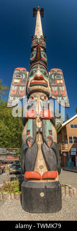 Sept. 17, 2018 - Ketchikan, AK: Tall panoramic of beautiful and very tall Chief Johnson Totem Pole with clear dark blue sky and local buildings. - Stock Image