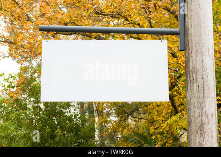 Advertising empty white blank board hanging on a wooden pole on the left, with nature forest in the background. Copy space available for text - Stock Image