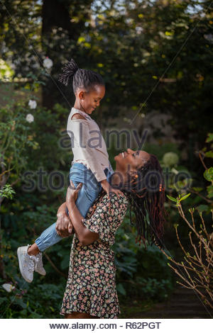 A mother lifting her daughter up in a garden - Stock Image