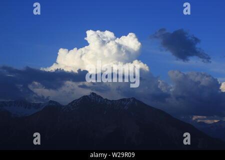 Cumulus cloud over Mount Lenzer Horn, Switzerland - Stock Image