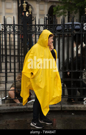 London, UK. 18th June 2019.  Tourist in plastic yellow raincoat at the Charing Cross Underground Exit on Trafalgar Square, London not sure what to make of this weather. Tourist and Londoners protecting themselves against the continuous rain in central London today.  Credit: JoeKuis / Alamy - Stock Image