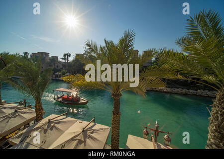 Canopied Arabian dhow makes its way down the blue waters of Souk Madinat Jumeirah and provides shade from the powerful desert sun in this lush oasis. - Stock Image
