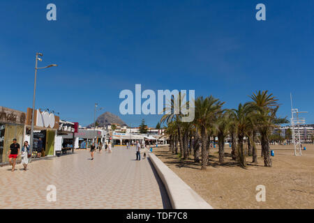 Xabia Spain Playa del Arenal paseo promenade with bars and shops beach in summer with blue sky and people, also known as Javea - Stock Image
