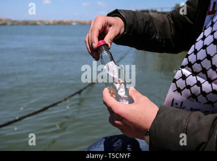 Gaza. 22nd Apr, 2019. A Palestinian seals a bottle with a letter in it before tossing it into the sea, at Gaza's fishing harbor in Gaza City, April 22, 2019. Dozens of Palestinian youths in Gaza City have sent letters to countries around the world, demanding solution to their problems and the lift of Israel's blockade on the Gaza Strip. These letters were written on Monday during an event held at Gaza's fishing harbor, before being sealed in small bottles and tossed into the sea. Credit: Yasser Qudih/Xinhua/Alamy Live News - Stock Image