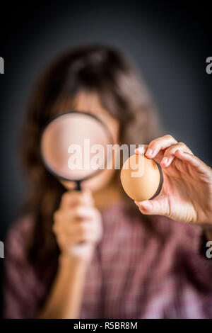 Woman watching an egg with a magnifying glass. - Stock Image