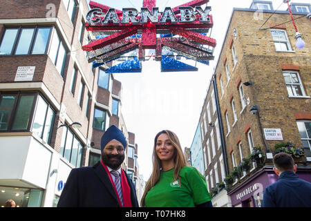 """London, UK. 18th March, 2019. Ranjit Baxi, Founding President of the Global Recycling Foundation, and Taekwondo World Champion Samira El Idrissi mark the celebration of the second annual Global Recycling Day beneath the Carnaby Street sign. This year's theme is """"Recycling into the Future"""", focusing on the importance and power of youth, innovation and education in ensuring a brighter future for the planet. Credit: Mark Kerrison/Alamy Live News - Stock Image"""