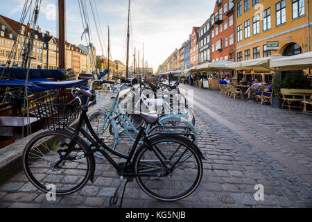 Bicycles and typical restaurants in the waterfront entertainment district of Nyhavn, Copenhagen, Denmark, Europe - Stock Image