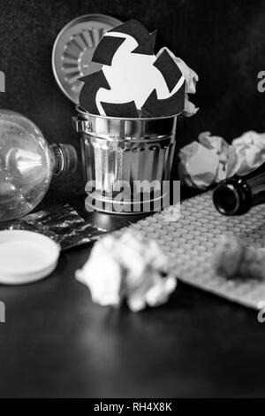 trash can with recycle symbol surrounded by reusable waste materials like plastic paper and glass, concept of reducing damage to the environment - Stock Image