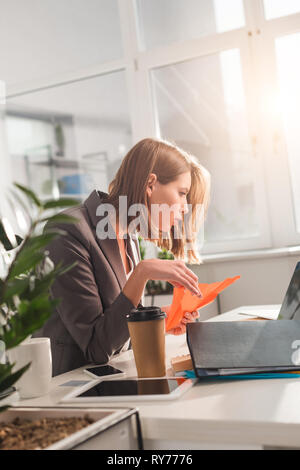 selective focus of woman holding paper plane and looking at laptop near disposable cup in office, procrastination concept - Stock Image