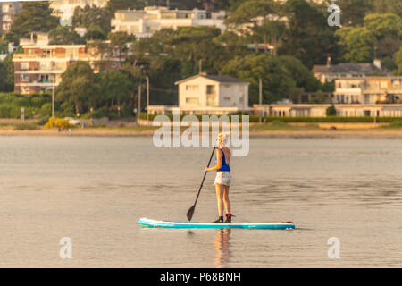 Poole, UK. 28th June 2018. UK weather. The sun sets over Poole Harbour on one of the hottest days on record. Paddleboarders get about with just an oar. Credit Thomas Faull / Alamy Live News - Stock Image