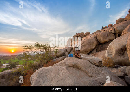 Tourists sitting on a sunset lookout spot in Hampi, India - Stock Image