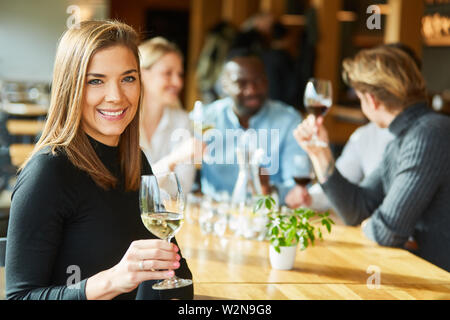 Young woman is drinking a glass of white wine together with friends in a pub - Stock Image