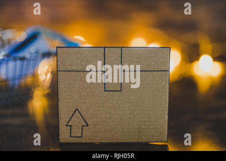 cardboard delivery parcel box on wooden desk with shopping basket and payment card with fairy lights in the background, concept of online purchases an - Stock Image