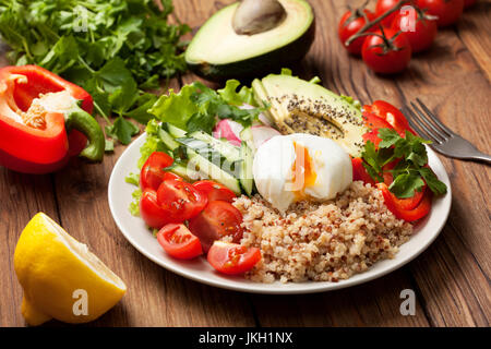 buddha bowl with mixture of vegetables, quinoa, poached egg  on wooden background - Stock Image
