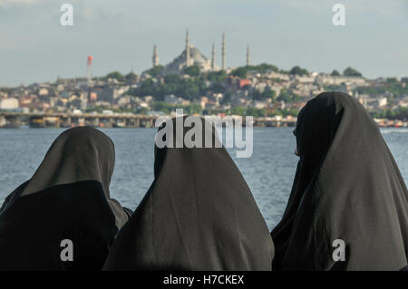 3 women in black islamic dress watch the scenery of the Golden Horn in Istanbul.   Suleymaniye mosque can be seen - Stock Image