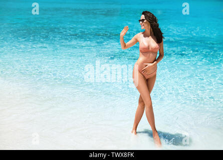 Alluring, young woman relaxing on a tropical beach - Stock Image