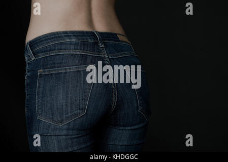 Close-up of woman's rear end in jeans - Stock Image