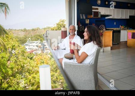 Couple sitting on balcony overlooking the marina of Nuevo Vallarta, Nayarit, Mexico - Stock Image