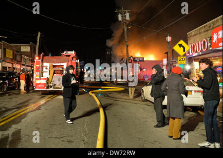 March 1, 2014 - Huntington, New York, U.S. - A large fire rages in the heart of Huntington village, on New York Avenue. Firefighters came from many surrounding towns of Suffolk County, Long Island, and huge clouds of smoke lit up the night sky for blocks. Credit:  Ann E Parry/Alamy Live News - Stock Image