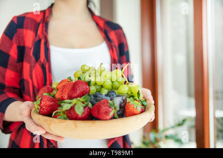 Woman holds wooden bowl with green grapes, strawberries and blueberries with window in the background. - Stock Image