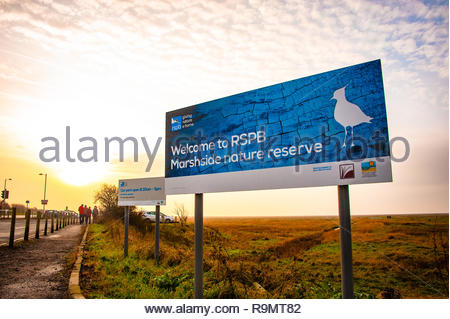 RSPB Marshside Nature Reserve 'Welcome to RSPB Marshside' sign in Southport, the light starts to fade at the end of a winters day on Merseyside, Lancashire, England UK Credit: Christopher Canty Photography/Alamy Live News - Stock Image