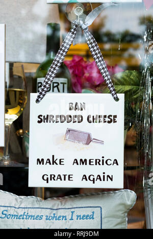 A funny sign outside a shop in Palm Beach, Florida making fun of Trump's slogan by saying 'Ban shredded cheese. Make America grate again.' - Stock Image