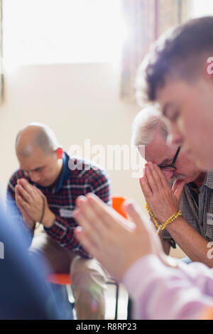 Men praying with prayer beads in prayer group - Stock Image