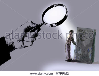 Hand holding magnifying glass over man hiding money - Stock Image