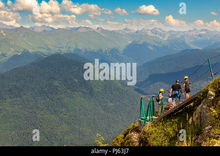Young woman crossing the chasm on the rope bridge, Sochi, Russia - Stock Image