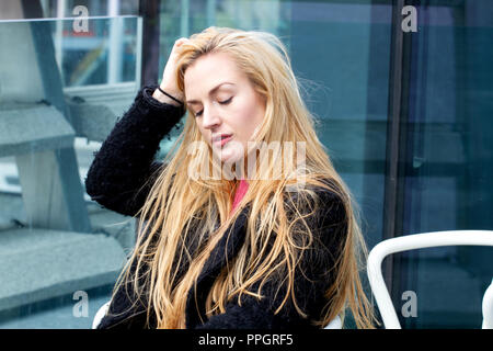 Dundee, Tayside, Scotland, UK. 25th September, 2018. UK weather: Strong winds with light rain sweeping across Tayside. A young blonde woman Rhianna Martin pays her first visit to the stunning new V&A building sitting outside on the Museum`s balcony on a very windy day in Dundee, UK. Credits: Dundee Photographics / Alamy Live News - Stock Image
