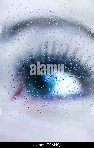 woman blue eye behind a glass with drops of water - image for book cover - Stock Image