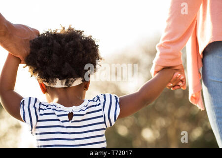 African American little girl holding hands with her parents. - Stock Image