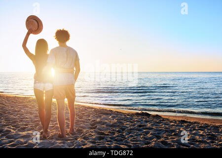 Couples during a sunrise at the beach - Stock Image