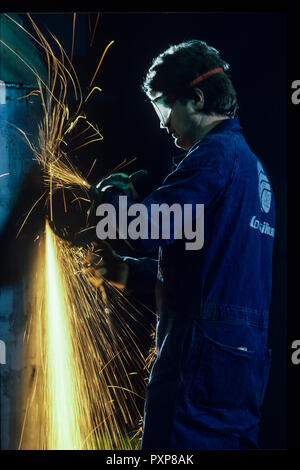 A  metal worker with an angle grinder, also known as a side grinder or disc grinder, doing abrasive cutting with a shower of sparks - Stock Image