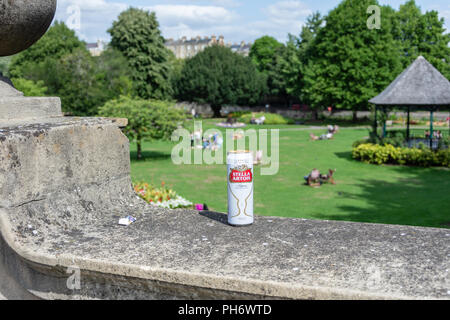 A can of Stella Artois left on top of a wall surrounding Parade Gardens with the bandstand in the background in the city of Bath - Stock Image