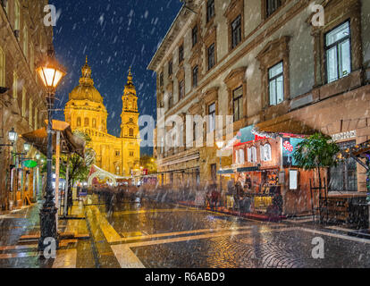 Budapest, Hungary - Snowy night at a Christmas market and shopping street with street-lamp, festive decoration and St.Stephen's basilica at background - Stock Image