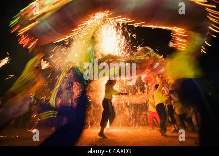 Thailand, Ko Phuket, Phuket.  Dragon dancers and fireworks during the Phuket Vegetarian Festival. - Stock Image