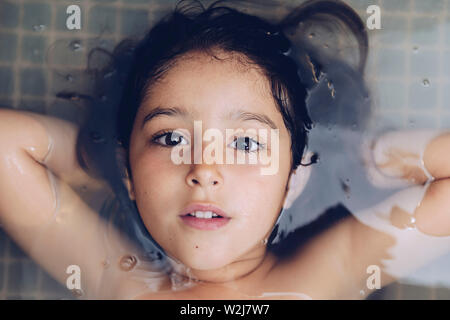 portrait of a happy beautiful little girl lying in the tub while taking a bath in the bathtub, kids hygiene concept - Stock Image