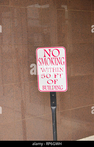 Sign posted next to front door of office building warning No Smoking within 50 Feet of Building, a caution sign for no smoking in Montgomery AL, USA. - Stock Image