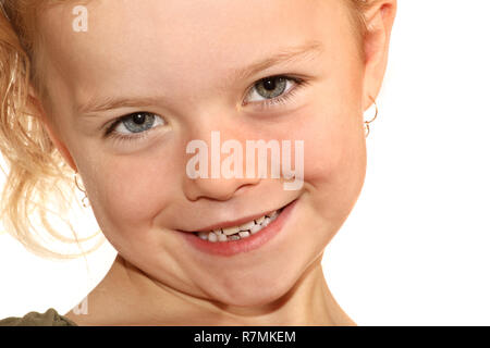 A close up image of a six year old girl smiling at the camera - Stock Image