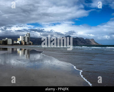 Strand's sandy beach on the shores of the South Atlantic with the Cape Peninsula mountains in the background, near Cape Town, South Africa - Stock Image