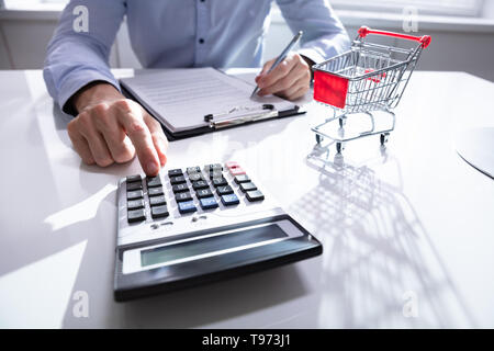 Close-up Of Man Calculating Shopping Expenses Near Shopping Trolley - Stock Image