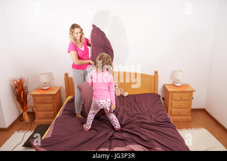 Happy family fighting with pillows - Stock Image