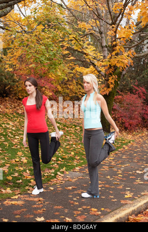Two young women stretching their legs during autumn. - Stock Image