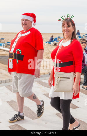 Benidorm, Costa Blanca, Spain, 25th December 2018. British tourists dress for the occasion on Christmas Day in this favourite getaway destination for Brits escaping the cold weather at home. Temperatures will be in the mid to high 20's Celsius today in this mediterranean hotspot. Middle aged couple wearing Christmas Jumpers and hats walking outside on the sea front promenade on Levante Beach looking at camera. - Stock Image