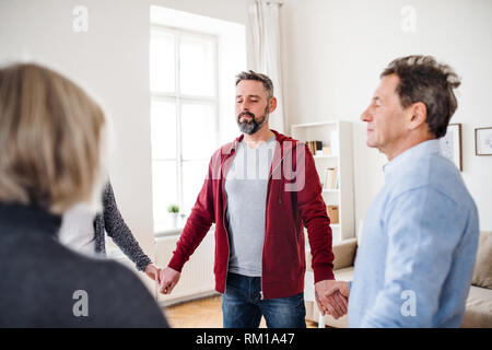 Group of people with closed eyes standing in a circle and holding hands during therapy. - Stock Image