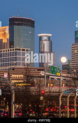 Full moon rises between buildings on the Minneapolis skyline. - Stock Image