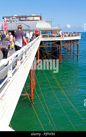 A view of people crabbing with lines over the side of the Pier at the North Norfolk resort of Cromer, Norfolk, England, United Kingdom, Europe. - Stock Image