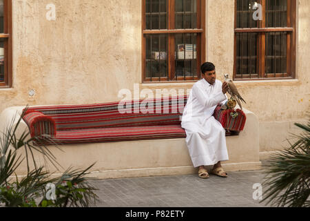 Young man holding a falcon in Souq Waqif, Doha, Qatar - Stock Image