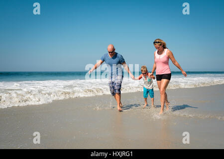Family of 3 walking and splashing water on the beach - Stock Image
